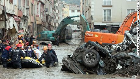 A rescue team evacuates residents in a boat in a residential area affected by heavy floods.