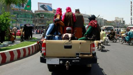 Taliban fighters sit on the back of a vehicle in the city of Herat, west of Kabul on Saturday.