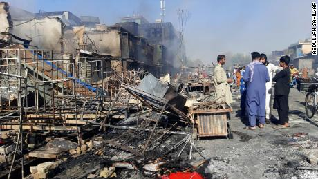 Afghans in Kunduz inspect damaged shops after fighting between Taliban and Afghan security forces on Sunday.