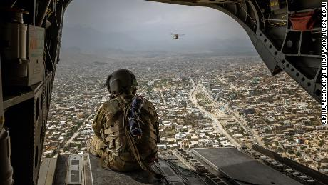 An American soldier sits on a CH-47 Chinook helicopter flying over Kabul on May 2, 2021.