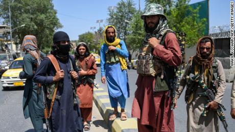 Taliban fighters stand guard along a street near Zanbaq Square in Kabul.