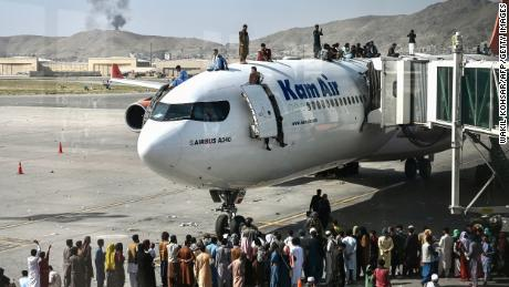 Afghans climb atop a plane amid scenes of chaos at Kabul's international airport.