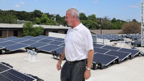 Matthew Haines, an independent rental owner near Dallas, inspects a solar array installed on top of one of his buildings earlier this summer.