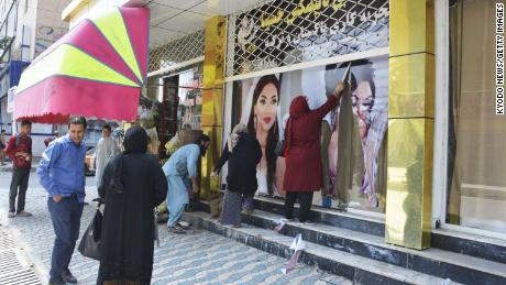 Workers at a beauty salon strip large photos of women off the wall in Kabul on August 15, 2021.