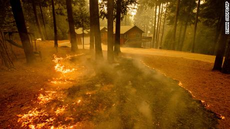Flames from the Caldor Fire scorch the ground near a structure in Grizzly Flats on August 18, 2021.