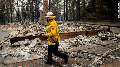 Cal Fire Division Chief Carmel Barnhart inspects a property after the Caldor Fire burned through Grizzly Flats, California.