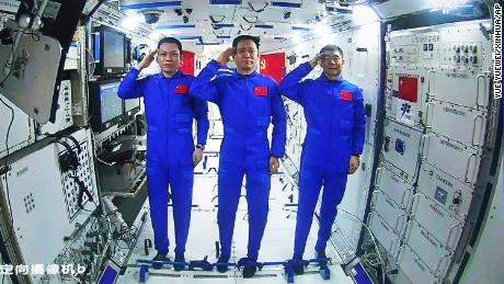 Chinese astronauts, from left Tang Hongbo, Nie Haisheng, and Liu Boming salute from aboard China's space station core module on June 23.