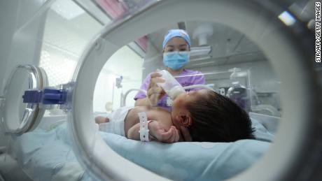 A medical staff member feeds a baby at a hospital in Danzhai, in China's southwestern Guizhou province on May 11, 2021.