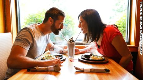Walker Hayes and wife Laney Beville Hayes splitting a shake at an Applebee's.