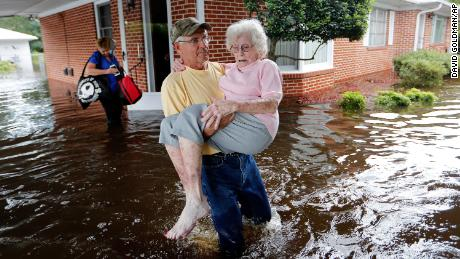 In the aftermath of Hurricane Florence in 2017, Bob Richling carries Iris Darden out of her flooded North Carolina home as her daughter-in-law, Pam Darden, gathers her belongings.