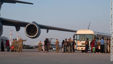 A group of Afghan evacuees depart a C-17 Globemaster III aircraft at Ramstein Air Base, Germany.