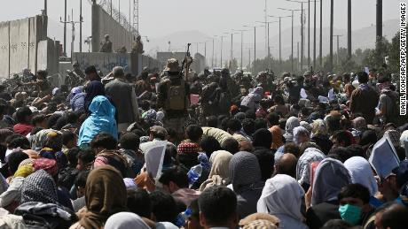 TOPSHOT - Afghans gather on a roadside near the military part of the airport in Kabul on August 20, 2021, hoping to flee from the country after the Taliban's military takeover of Afghanistan.