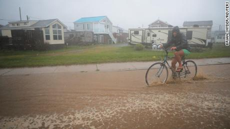 A bicyclist rides through a flooded street as Tropical Storm Henri approaches South Kingstown, Rhode Island, U.S., August 22, 2021.   REUTERS/Brian Snyder