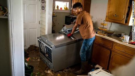Kalyn Clayton, 16, surveys the damaged kitchen of a home while volunteering with his church youth group in Waverly, Tennessee.