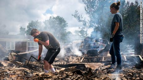 Josh Whitlock and Stacy Mathieson look through what is left of their home after it burned following flooding in Waverly, Tennessee.