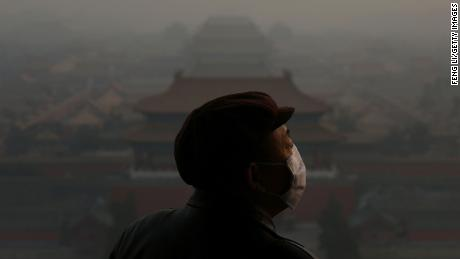 A tourist wearing a face mask looking at the Forbidden City through heavy smog in Beijing, China, on January 16, 2013.