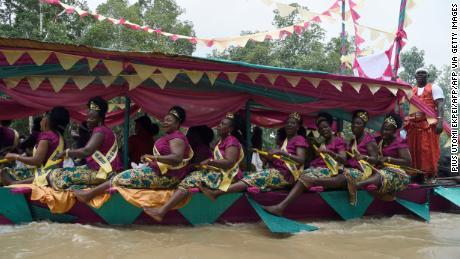 Women dance in a regatta to mark the coronation of Prince Tsola Emiko as the 21st king or the Olu of Warri kingdom and the Ogiame Atuwatse 111 at Ode Itsekiri.
