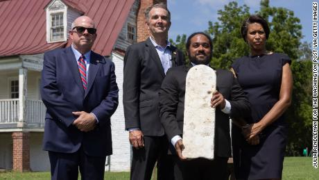 Nathan Burrell, with the Virginia Department of Conservation and Recreation, holds a grave marker and poses with, from left,  Govs. Larry Hogan  Ralph Northam and Washington, DC, Mayor Muriel Bowser after a ceremonial gravestone transfer Monday