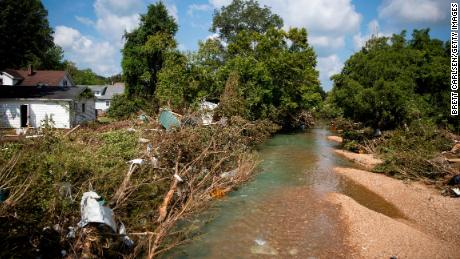 Debris can be seen Monday in the brush around a creek that rose to deadly levels over the weekend in Waverly, Tennessee.