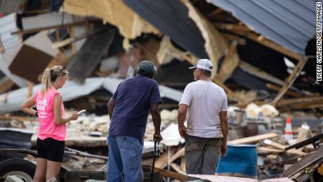 People watch cleanup efforts Monday after buildings were destroyed by flooding in Waverly, Tennessee.