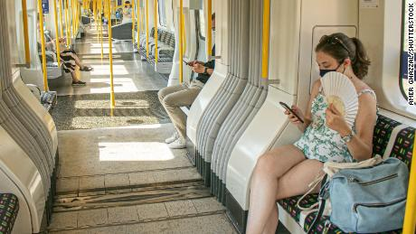A passenger on the London Underground attempts to stay cool during a heat wave in August 2020.