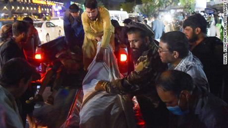 Volunteers and medical staff unload bodies from a pickup truck outside a hospital after the explosion outside the airport in Kabul on August 26.