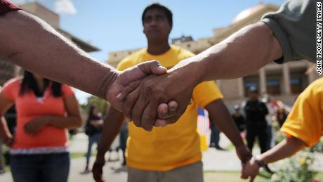 Demonstrators protesting a new immigration law hold hands at the Arizona Capitol on April 23, 2010.