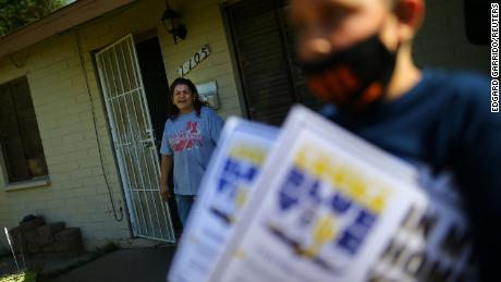 A resident watches people distribute posters during a political event in Phoenix on October 31.