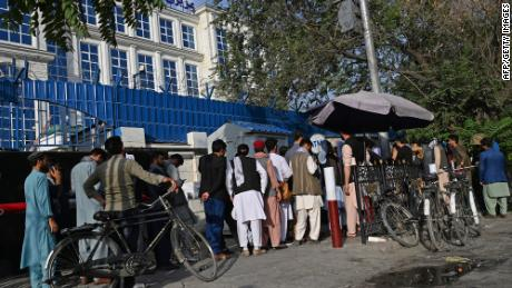People in Afghanistan wait in line to withdraw money from an ATM in Kabul on August 21.