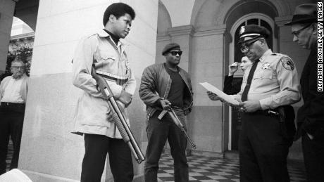 Two members of the Black Panther Party are met on the steps of the state capitol in Sacramento, California, May 2, 1967.