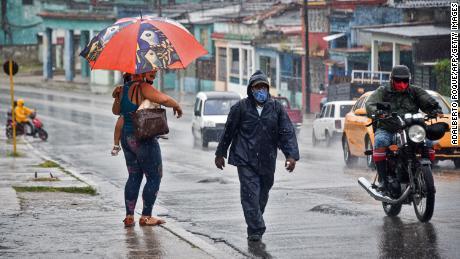 People walk under the rain in Havana on August 27, 2021, as Hurricane Ida passes through eastern Cuba.