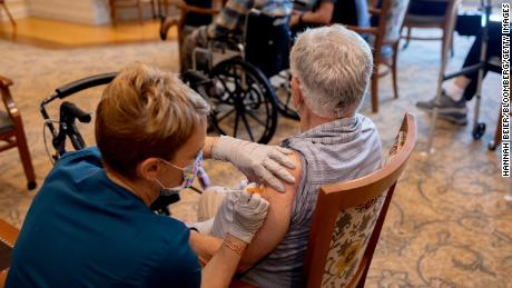A healthcare worker administers a third dose of the Pfizer-BioNTech Covid-19 vaccine at a senior living facility in Worcester, Pennsylvania.