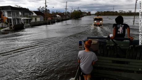 Catera Whitson (C) and Kyler Melancon (R) ride in the back of a high water truck Monday as they volunteer to help evacuate people from homes after neighborhoods flooded in LaPlace, Louisiana, due to Hurricane Ida.