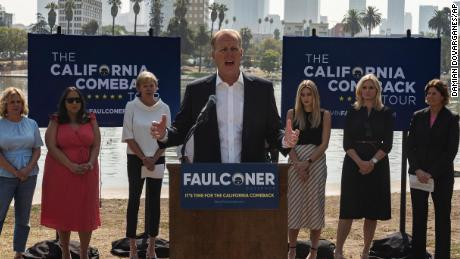 """California gubernatorial candidate and former San Diego mayor Kevin Faulconer, center, speaks to the media at a campaign stop to promote his """"women's empowerment plan"""" at MacArthur Park in Los Angeles Monday, Aug. 30, 2021."""