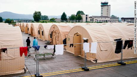 People evacuated from Afghanistan stand between tents at Ramstein.