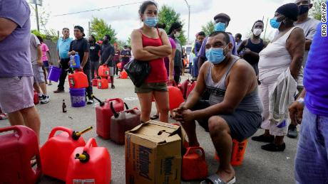 In the aftermath of Hurricane Ida, people wait in line for gas Tuesday in New Orleans.
