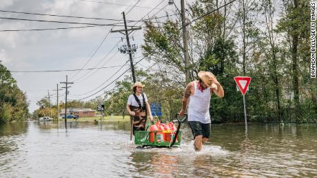 Residents move a cart with gas cans through a flooded neighborhood on Tuesday in Barataria, Louisiana.