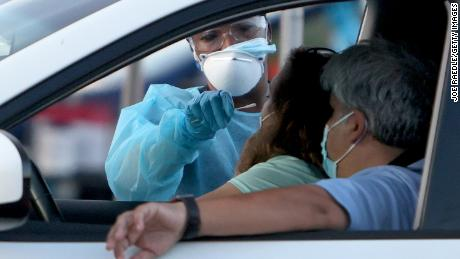 A healthcare worker at a 24-hour drive-thru site set up by Miami-Dade and Nomi Health in Tropical Park administers a Covid-19 test on Monday in Miami, Florida.