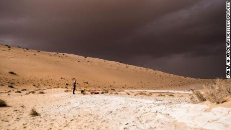 A storm arrives during archaeological excavation of an ancient lake.