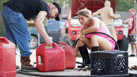 A woman fills a customer's gas can in Maurepas, Louisiana, on September 1, 2021.