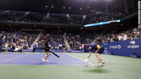 Crew members do their best to dry the court.