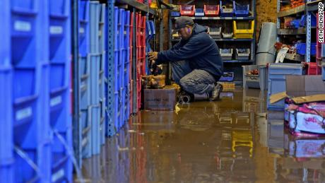 An employee helps clean up after the business he works at was flooded in Woodland Park, New Jersey.