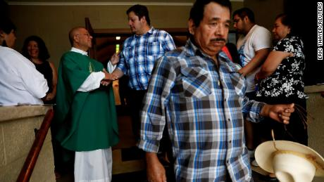 A priest greets worshippers after leading a Spanish-spoken church service in West Liberty, Iowa, on August 25, 2019.