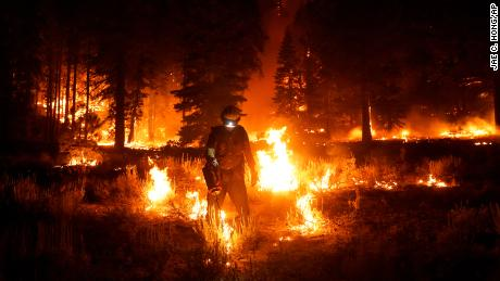 A firefighter lights a backfire to stop the Caldor Fire from spreading near South Lake Tahoe on September 1, 2021.