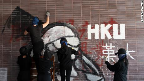 """Graffiti on a wall at HKU during the 2019 siege reads """"revolution university."""""""