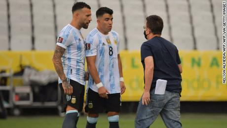 An employee of Brazil's National Health Surveillance Agency (Anvisa) argues with Argentina's Nicolas Otamendi (L) and Marcos Acuna.