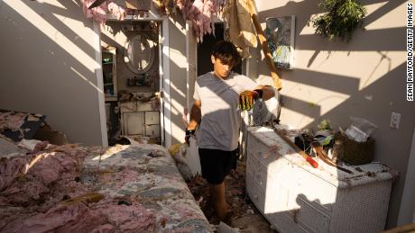 Michael Szeplaki helps to clean up his family's vacation house in the wake of Hurricane Ida on Saturday in Grand Isle, Louisiana.