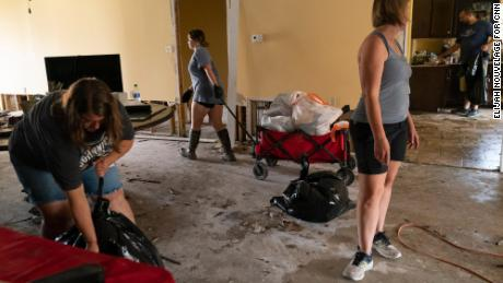 Cassie Falgoust, left, and her sister Michelle Smith, right, help clean out their parents' home.