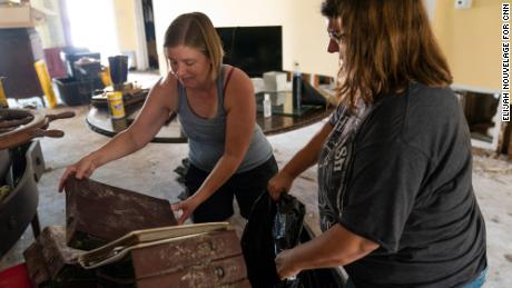 Michelle Smith, left, and her sister Cassie Falgoust throw out water-damaged family photo albums.