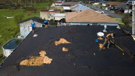 People work to repair a roof in Norco, Louisiana.